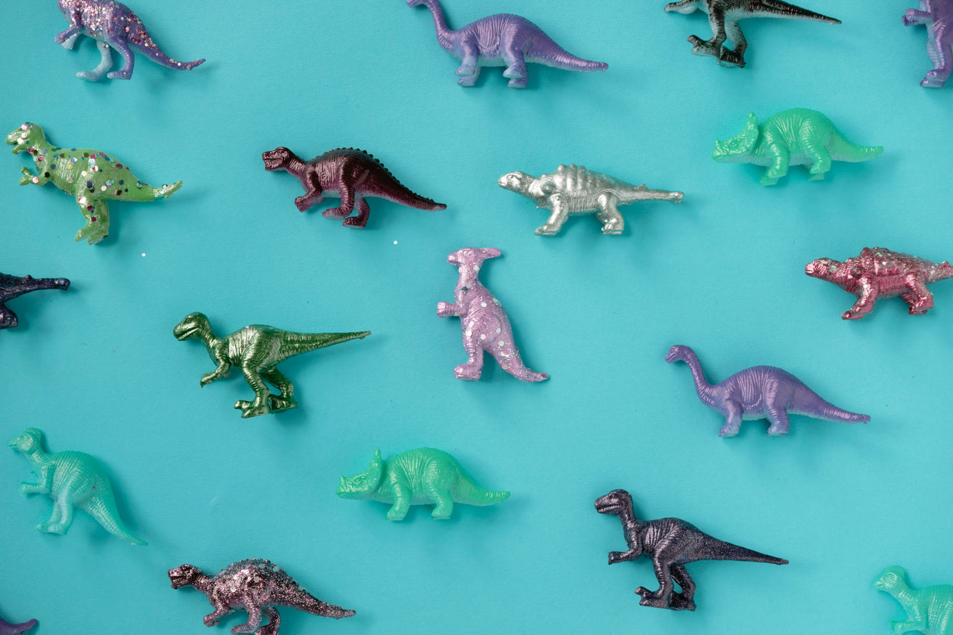 assorted color plastic dinosaur figurine lot on teal surface