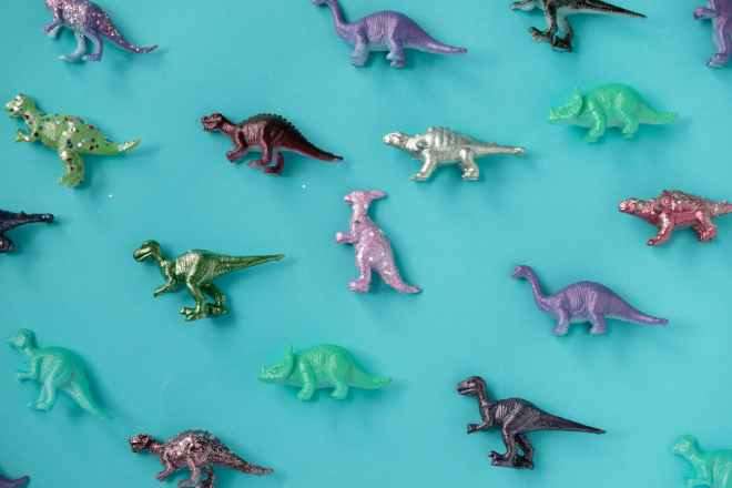assorted color plastic dinosaur figurine lot on teal surface